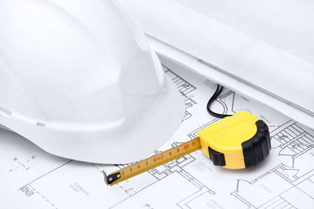 hard stuff: White hard hat and tape measure are on the opened design druft Stock Photo