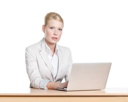 Young businesswoman sitting at a office desk with laptop, looking at the camera photo