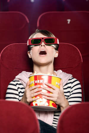 Young woman in 3D glasses watching a movie photo
