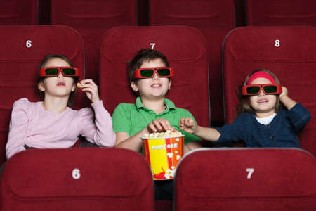 sits on a chair: Children watching a  movie at the 3D cinema Stock Photo