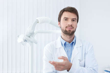 male dentist: Thoughtful dentist talks to the patient