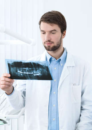thinks: Dentist thinks over the roentgenogram, whte background Stock Photo