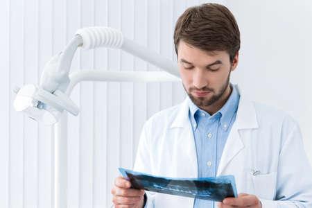 profundity: Dentist carefully studies the roentgenogram, whte background