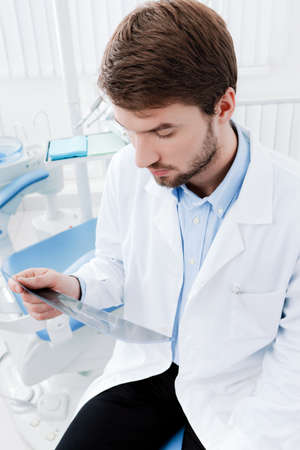 sits on a chair: Dentist deeply examines the roentgenogram, whte background Stock Photo