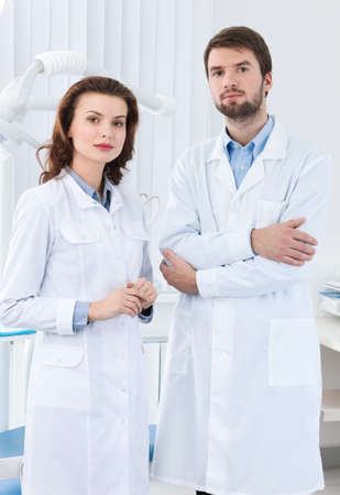 Dentist and his assistant wait the patient, white background photo