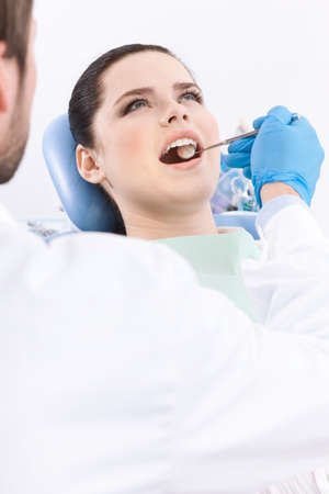 medical procedure: Dentist meticulously examines the oral cavity of the patient on the dentist