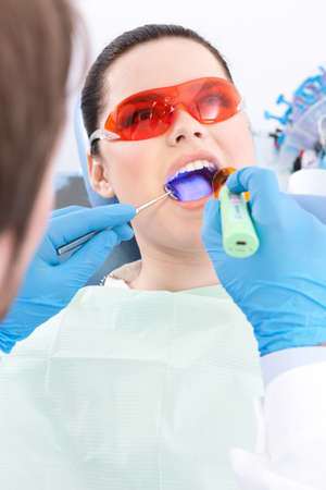 carious: Dentist uses photopolymer lamp to treat carious teeth of the patient