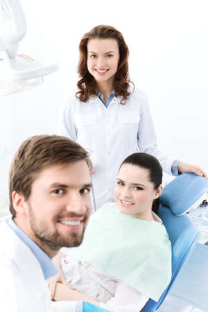 Dentist, his assistant and the patient are prepairing to treat carious teeth photo