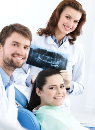 Dentist, assistant and client are satisfied of their work, close up photo