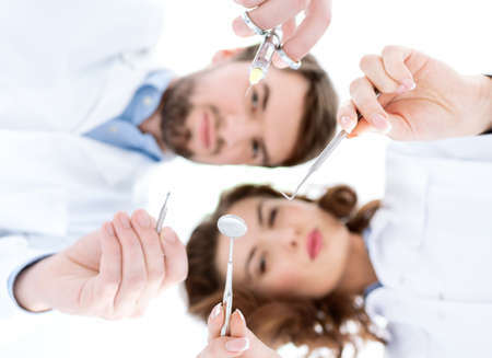 speculum: Dentist and his assistant show different medical instruments, the background is blurred