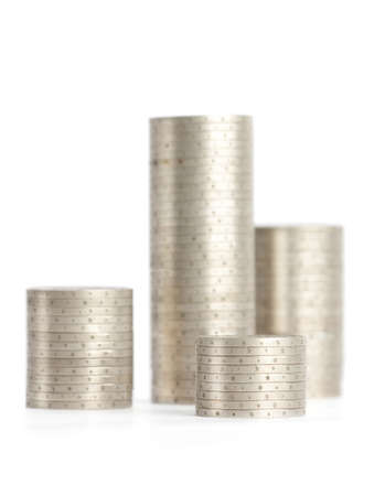 coin silver: Silver coins are erected vertically in columns, isolated on white  Symmetrically posed coins symbolize wealth, richness, income and profit  Close up shot