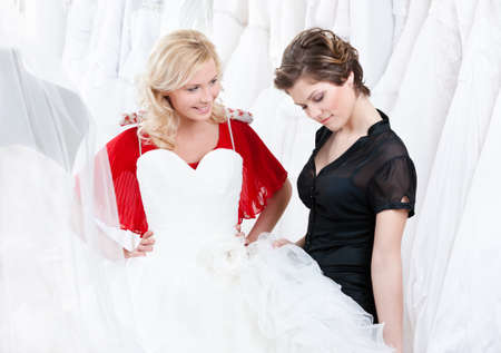 Young girl is thinking over a wedding gown Shop assistant helps her Stock Photo - 14729998