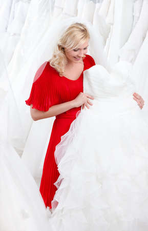 decides: Future bride chooses an appropriate wedding gown Stock Photo