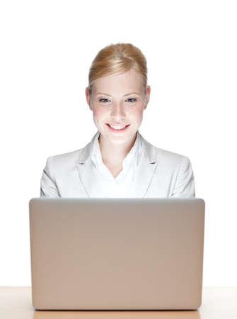 grigiastro: Sorridente giovane imprenditrice seduto a un tavolo con il computer portatile, isolato Archivio Fotografico