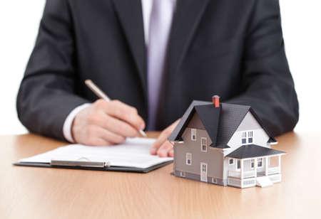 реальный: Понятие недвижимости - бизнесмен подписывает контракт за домом архитектурной модели
