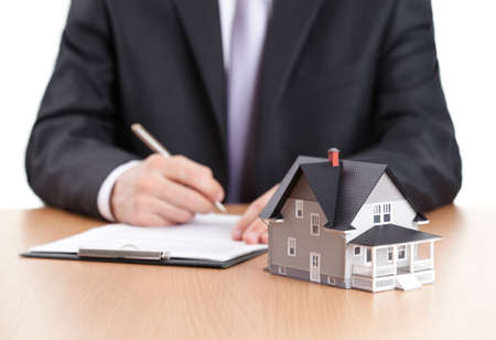 lending: Real estate concept - businessman signs contract behind home architectural model