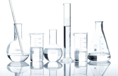 Group of laboratory flasks with a clear liquid, isolated photo