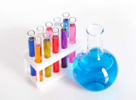 Group of test tubes in a rack and a flask with colored liquids, isolated photo