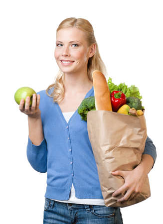 Young woman with a paper bag full of healthy eating, isolated on white photo