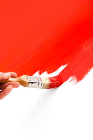 verb: Painting with red colored ink and paintbrush on white Stock Photo