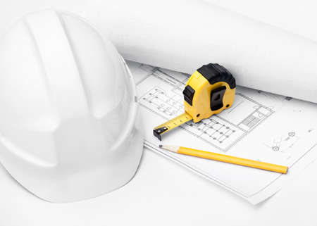 White hard hat, tape measure and pencil on the druft, isolated on white background photo