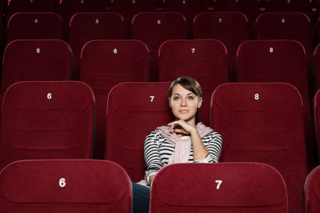 Young woman watching a movie alone photo