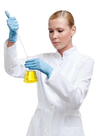 laboratorio clinico: Químico derrama algo en el líquido de color amarillo en el frasco, aislado en blanco