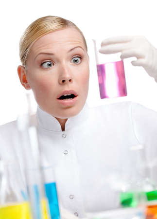 Young lady scientist wonders at the beaker full of purple liquid, isolated on white photo