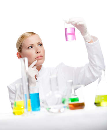 Young lady scientist stares at the beaker full of purple liquid, isolated on white Stock Photo - 14729946