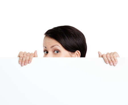 Beautiful young woman hides behind a huge sheet of white cardboard, isolated on white photo