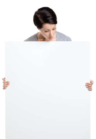 Woman brings a huge sheet of white cardboard, isolated on white photo