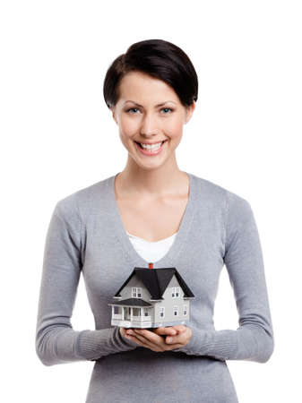Young woman hands small toy house in front of herself, isolated on white photo