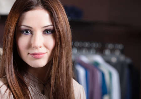 Attractive woman against the background of set of hanger clothes photo