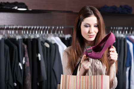 filles shopping: Femme regarde � chaussures fuchsia excellentes au centre commercial