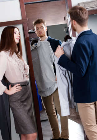 try on: Young man consults with girlfriend while selecting a spruce shirt