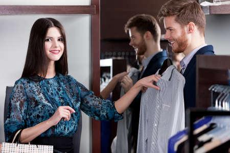 chicas comprando: Hombre joven que consulta con su novia mientras se selecciona una camisa elegante