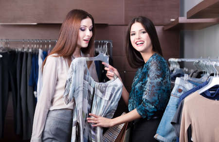 Friends do shopping and discuss a dress at the store photo
