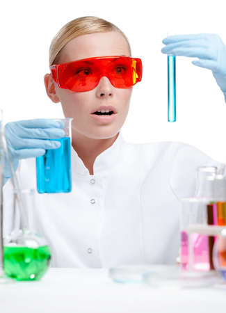 Wondered female doctor in spectacles does some experiments, isolated on white Stock Photo - 14847479