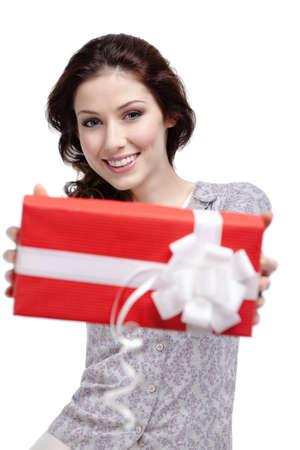 Jonge vrouw passeert een geschenk verpakt in rood papier, geïsoleerd op wit