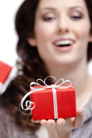 Young woman shows a gift wrapped in red paper, isolated on white, close up photo