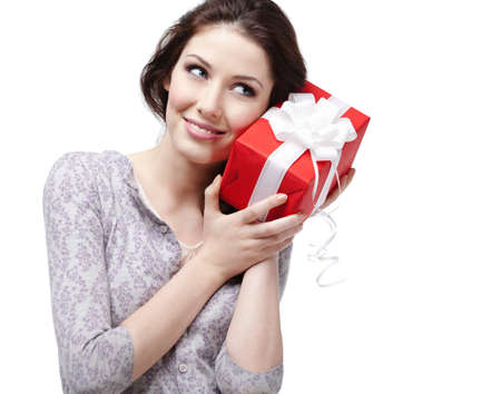 pry: Young woman puts her ear to the present wrapped in red paper, isolated on white