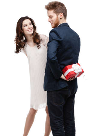 pry: Man conceals the present behind the back from his pretty girlfriend, isolated on white Stock Photo