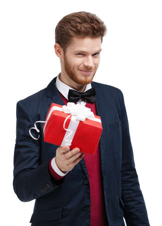 Man in bow tie offers a present wrapped in red gift paper, isolated on white Stock Photo - 14847530
