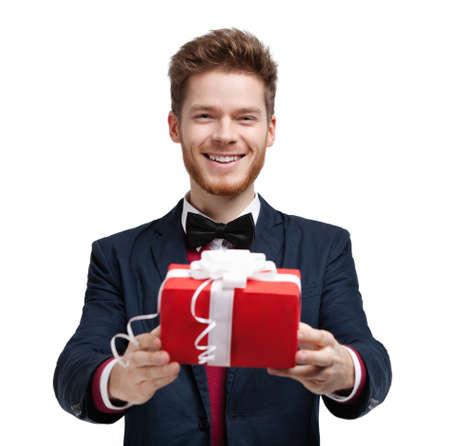 lazo regalo: El hombre da un regalo envuelto en papel de regalo rojo, aislado en blanco Foto de archivo