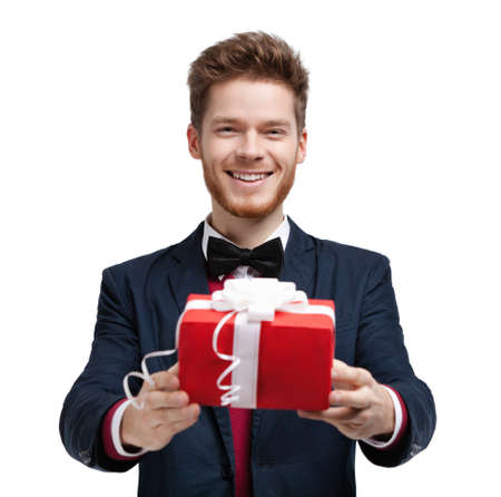 Man gives a present wrapped in red gift paper, isolated on white photo