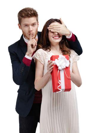 guardar silencio: Hombre haciendo el gesto de silencio cierra los ojos de su novia a dar un regalo, aislado en blanco Foto de archivo