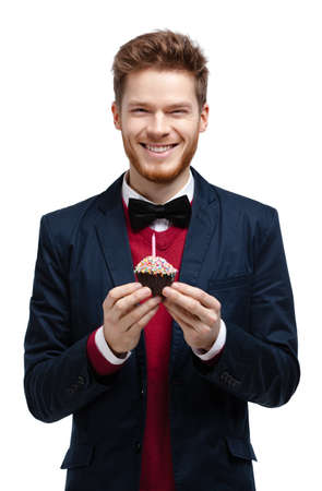 greets: Man in blue suit with bow tie holds small tart, isolated on white