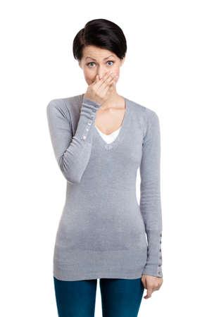 tufo: Mujer joven cierra la nariz con la mano, aislados en blanco