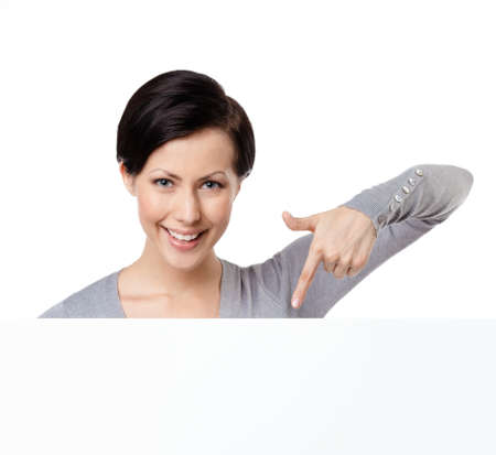 Young woman points down with forefinger , isolated on white photo