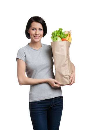 Girl keeps the packet full of healthy products, isolated, white background photo